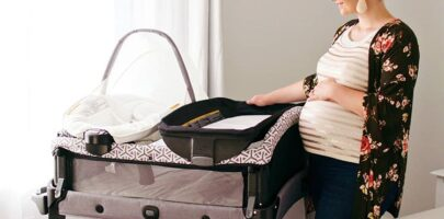 Mom stands by a Graco pack 'n play and holds her baby belly.
