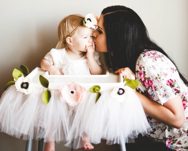 Mom kisses daugther during her floral first birthday party.