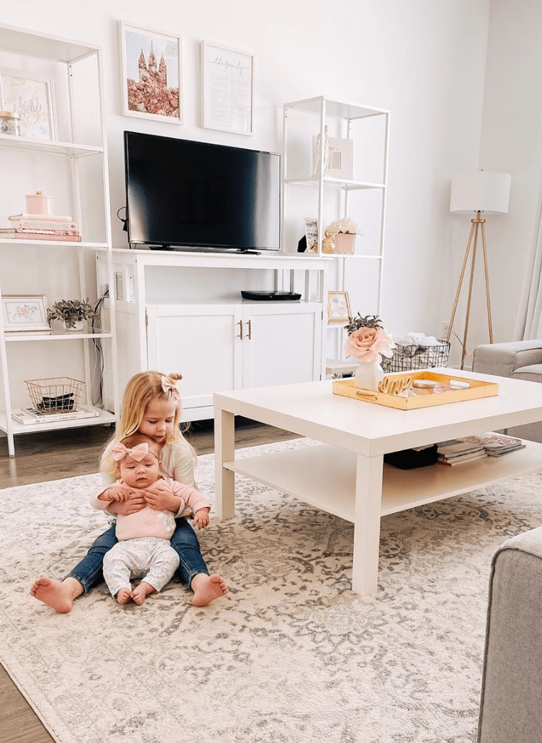 Sisters play in front of cute living room home decor.