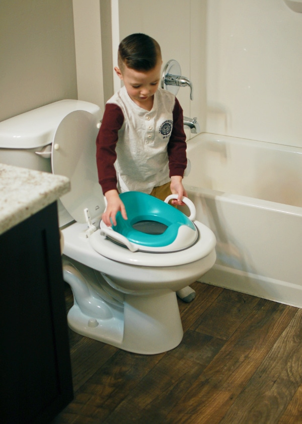 Boy puts training seat on potty.