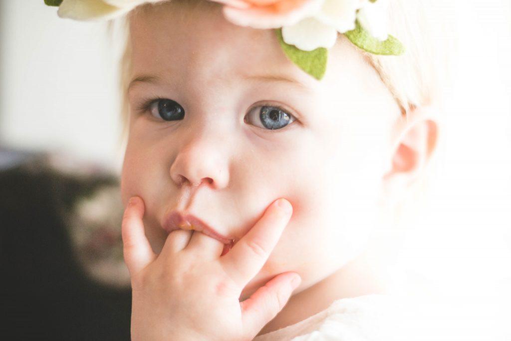 Toddler girl sucking her fingers.