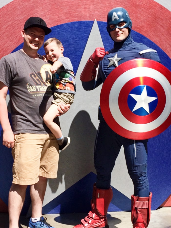 Father and son stand next to Captain American in California Adventure Park