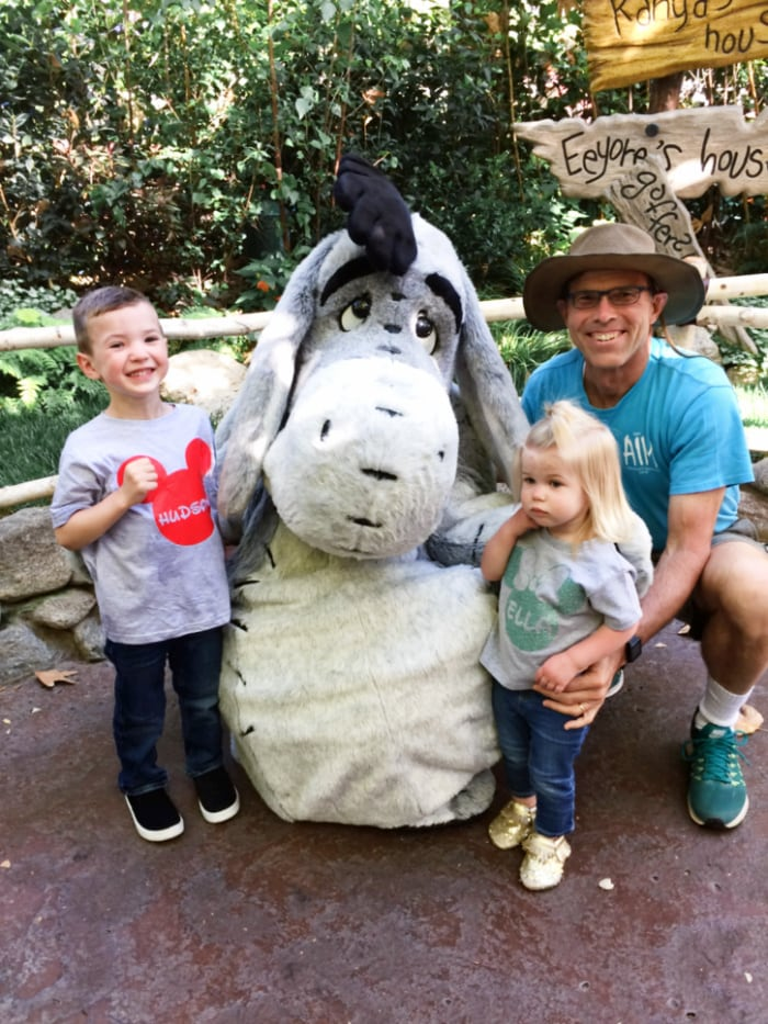 Family smiles next to Eeyore in Disneyland