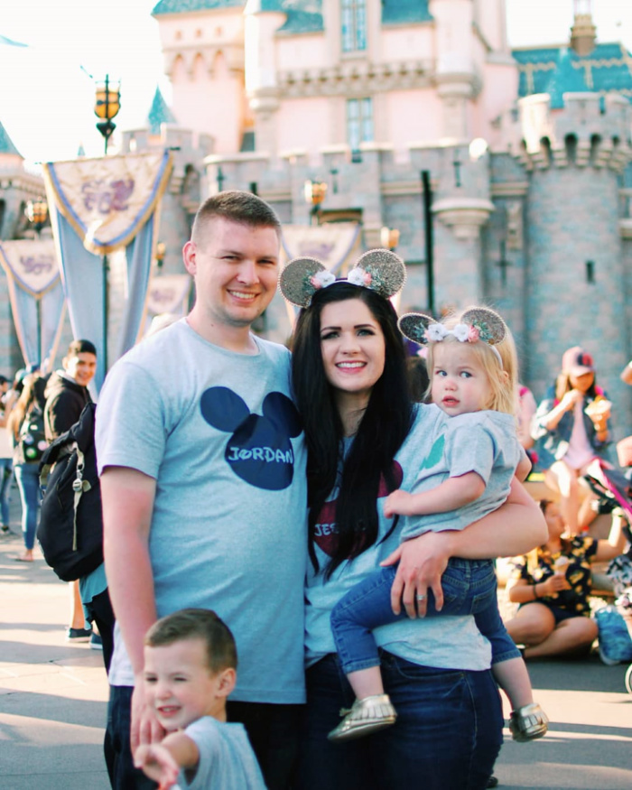 Family poses in front of Disneyland Castle.