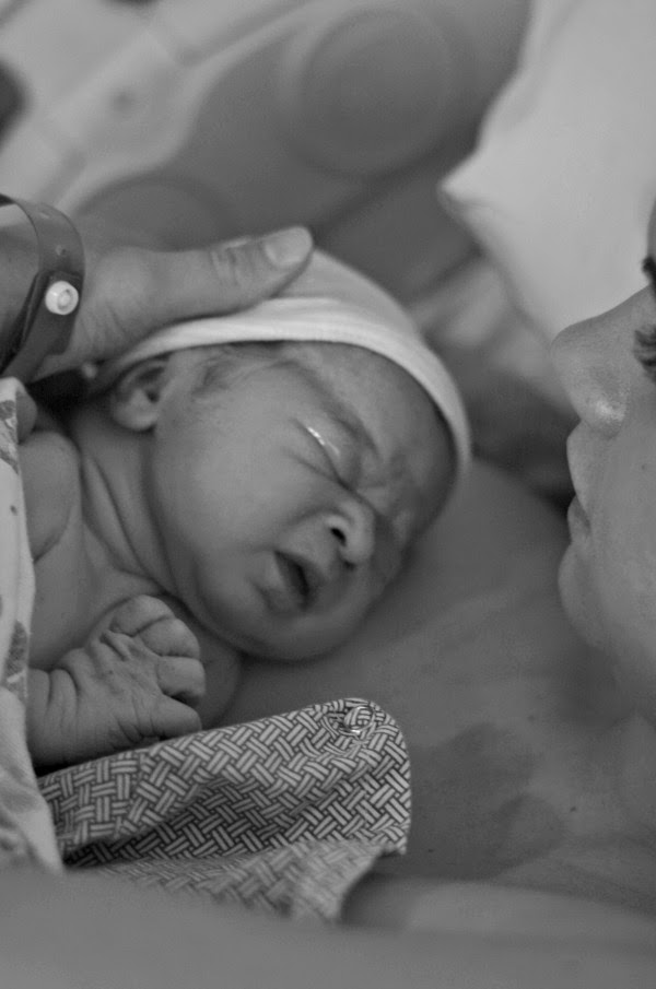 New mom holds baby boy after delivery and thinks about his name.