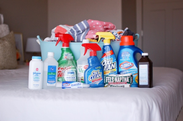 Clothing stain removal products next to a laundry basket