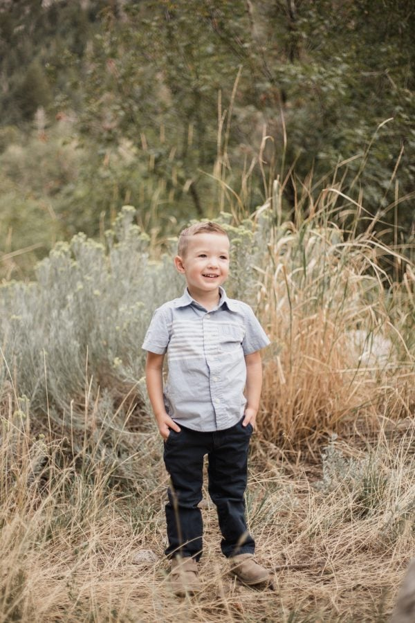 Toddler boy smiles during family photos.