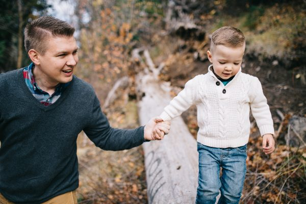 Dad holds son's hand during family pictures.