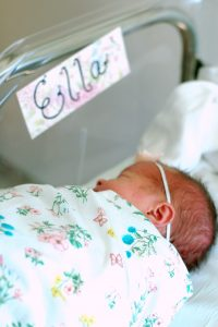 Baby in hospital bassinet with name tag from modern baby names list.