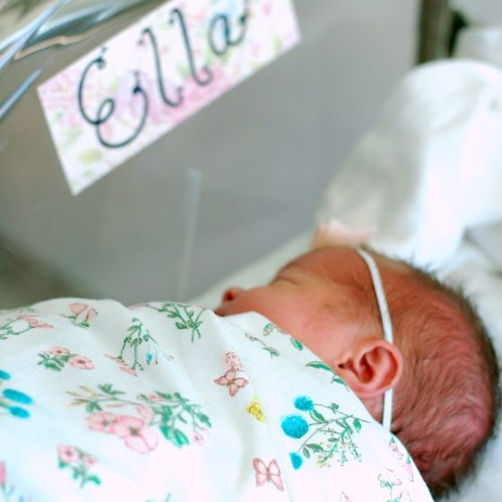 A newborn baby sits in her bassinet with her modern girl name written on a card above her.