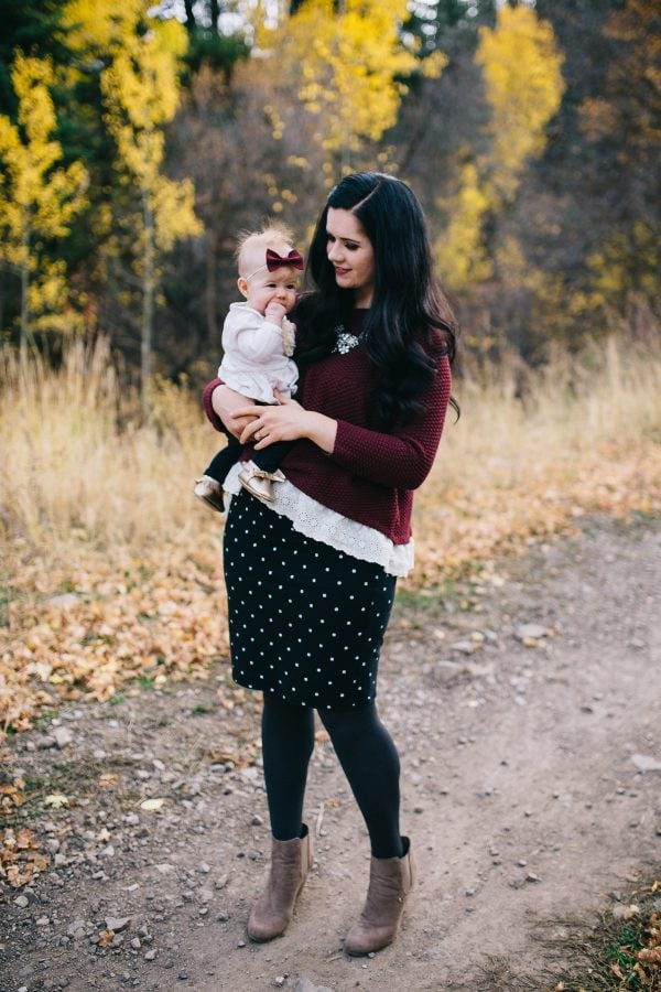 Mom holds baby girl during fall family pictures.