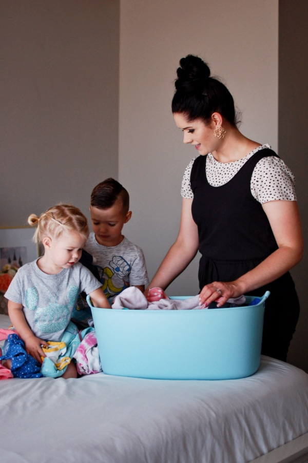 Mom and kids sort the laundry after cleaning them with stain remover products