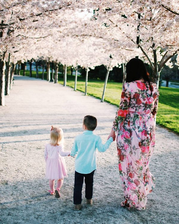 Family walks by blossoms during spring pictures.