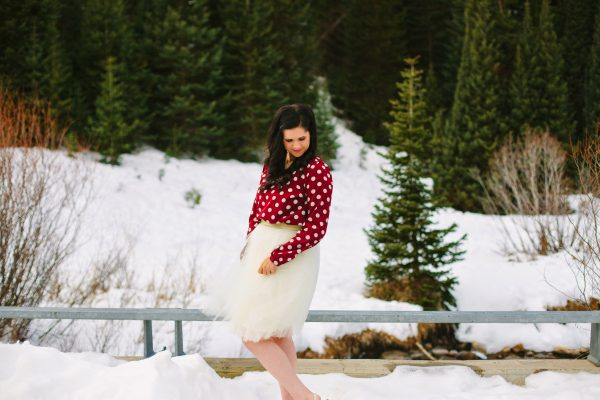Woman holds skirt and looks down during winter photos.