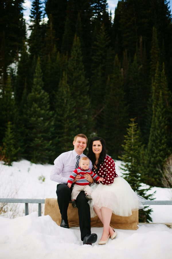 Couple holds baby boy and smiles during winter family photos.