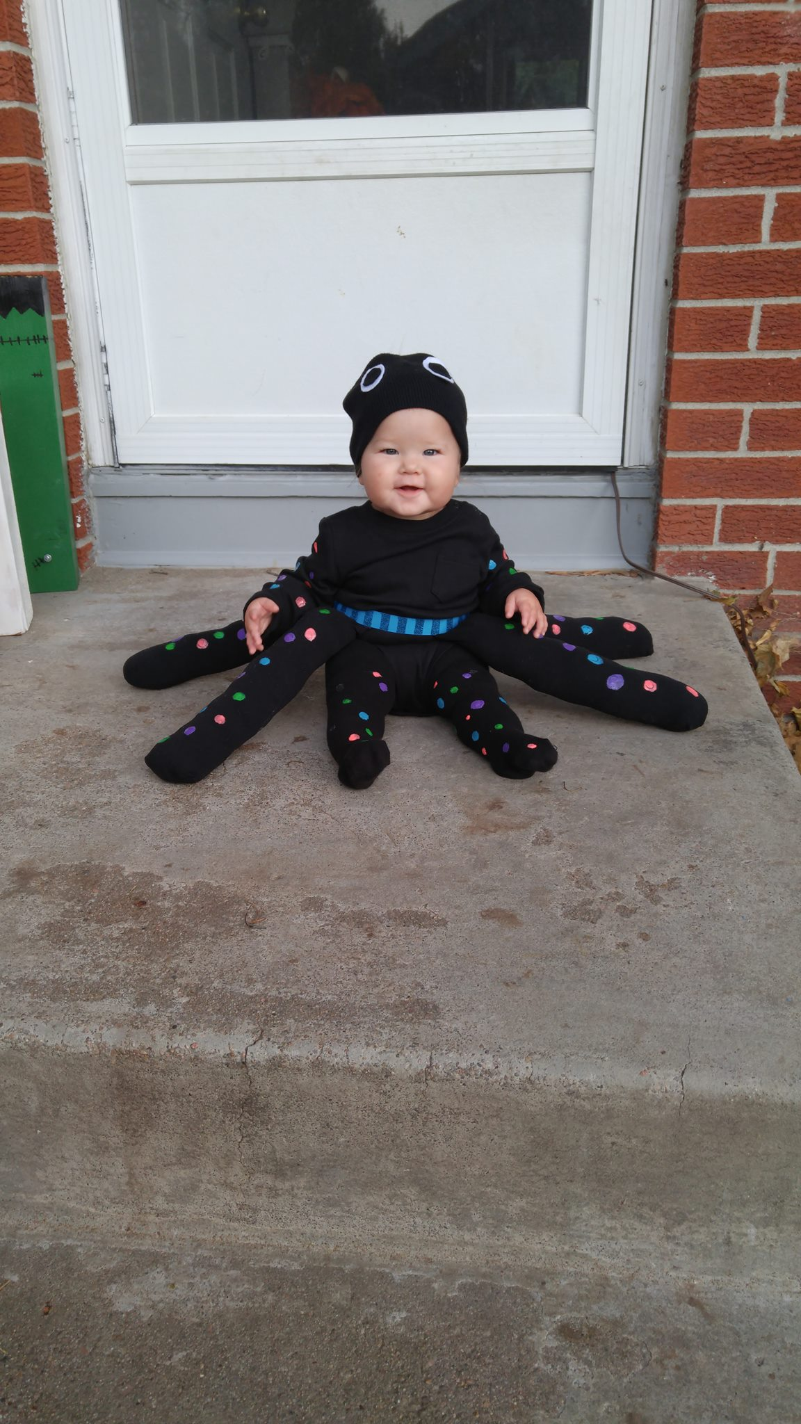 Baby girl wearing octopus Halloween costume sits on porch and smiles.