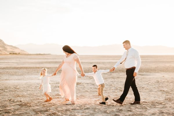 Family walks across beach in family pictures.