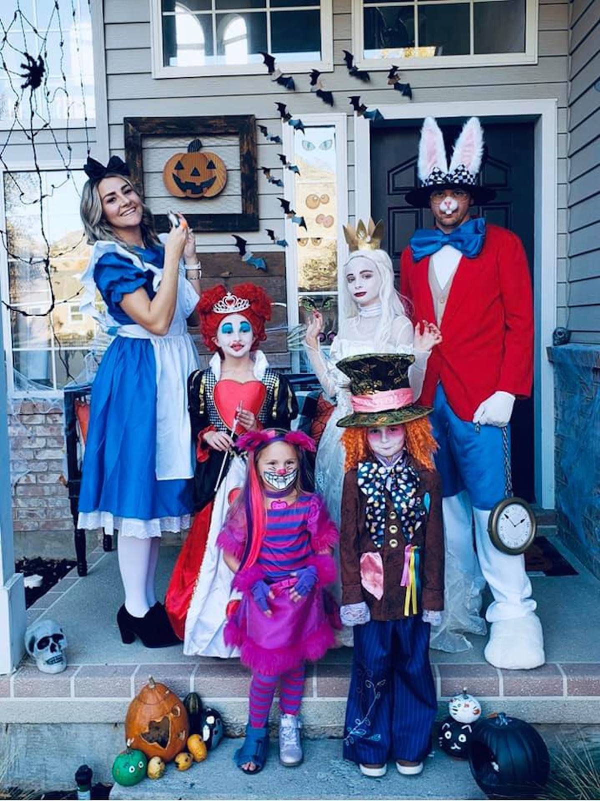 Family wearing Alice in Wonderland costumes stands on front porch and smiles.
