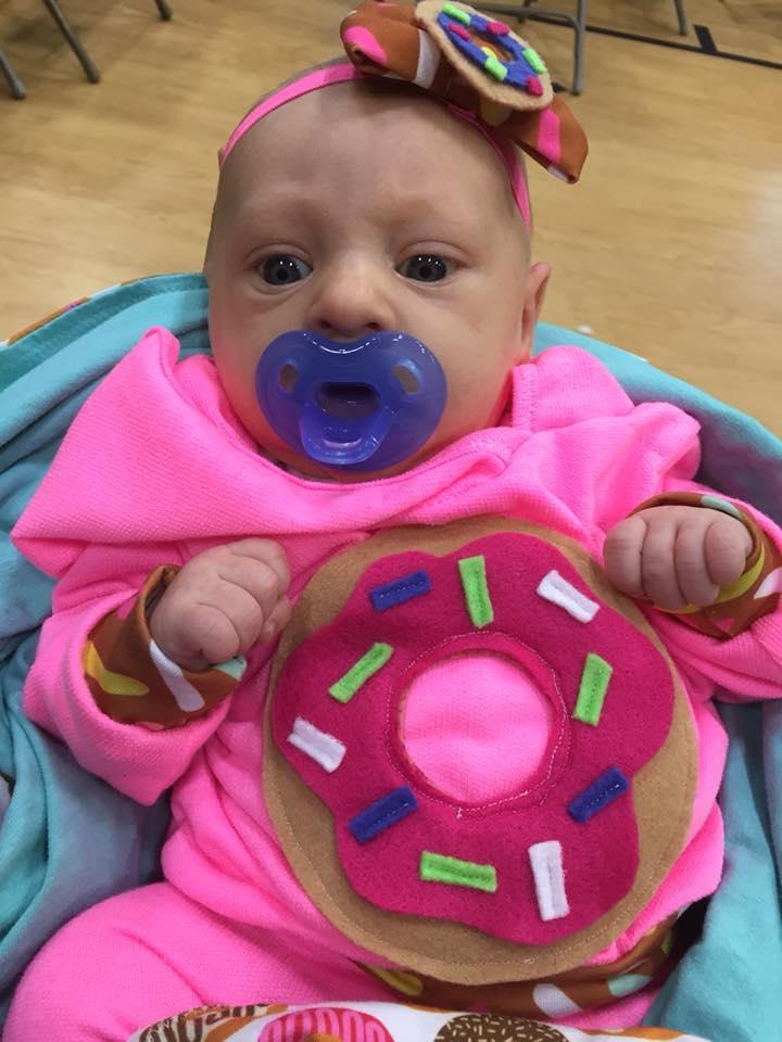Baby with a purple binkie wears a DIY donut Halloween costume.