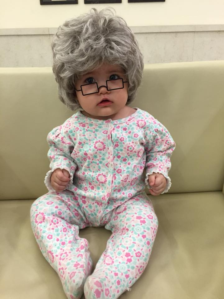 Baby girl wears DIY grandma baby Halloween costume and sits on a couch.
