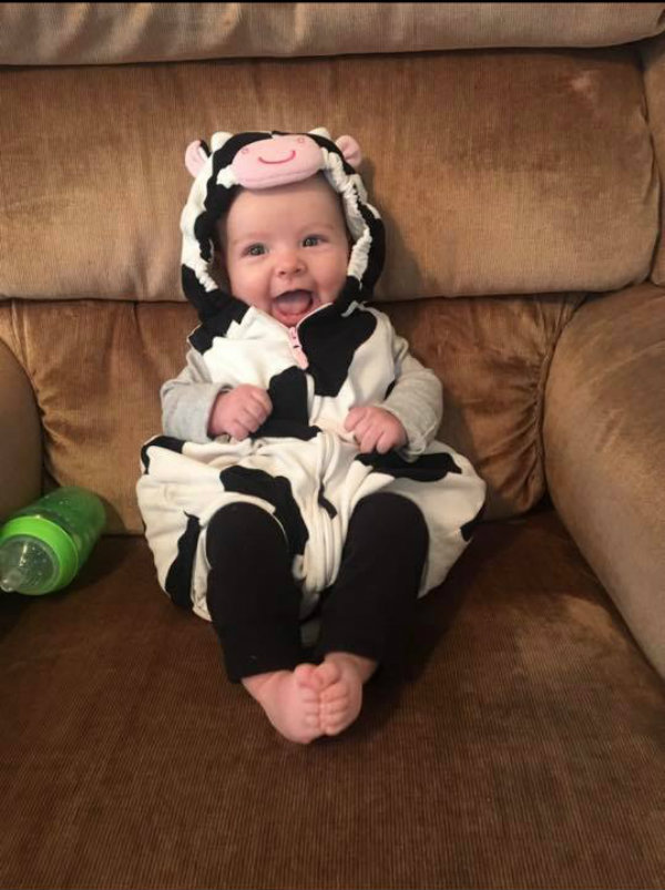 Baby smiles while wearing cow Halloween costume and sitting on recliner.
