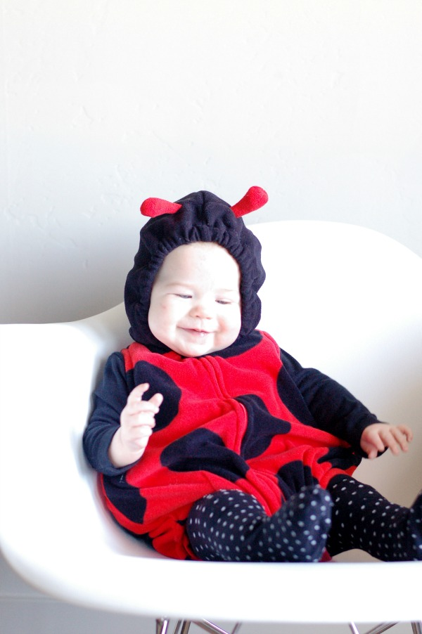Baby girl smiles while wearing a lady bug Halloween costume and sitting on white chair.