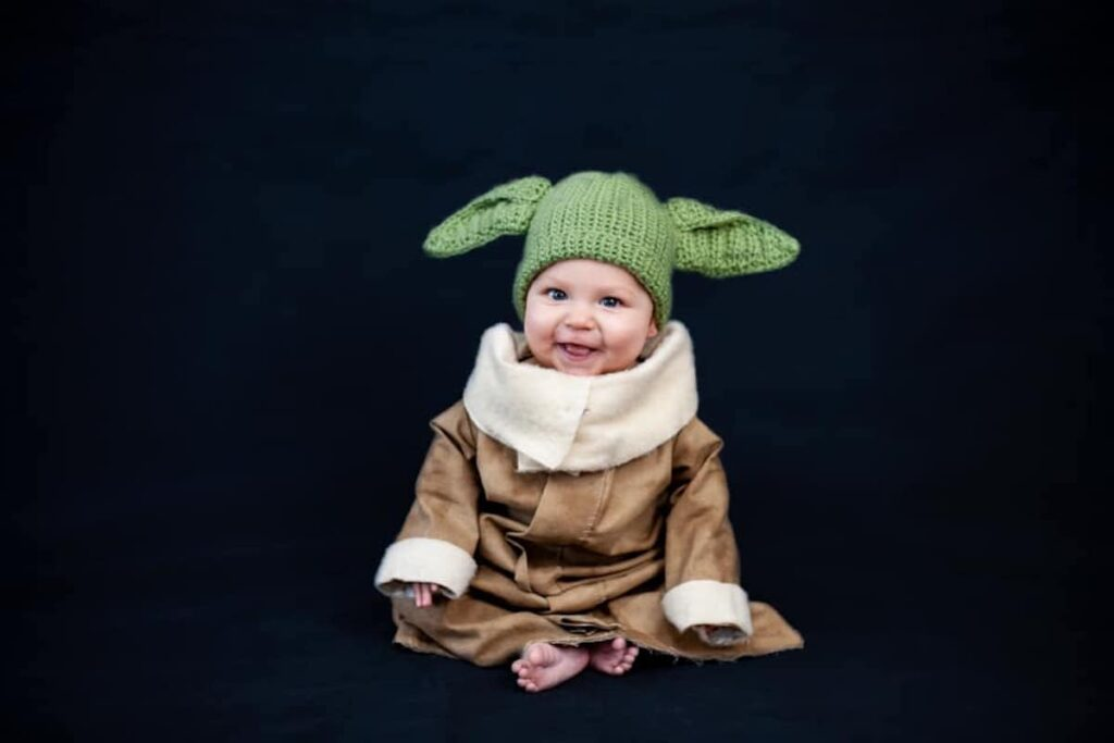 Baby wearing Baby Yoda costume sits in front of dark backdrop.