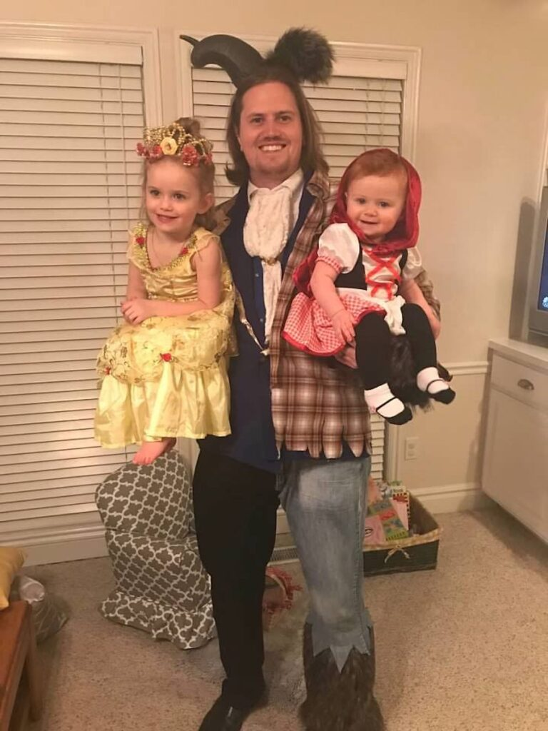 Man wearing beast and wolf costume holds one girl wearing Belle costume and one girl wearing Red Riding costume.