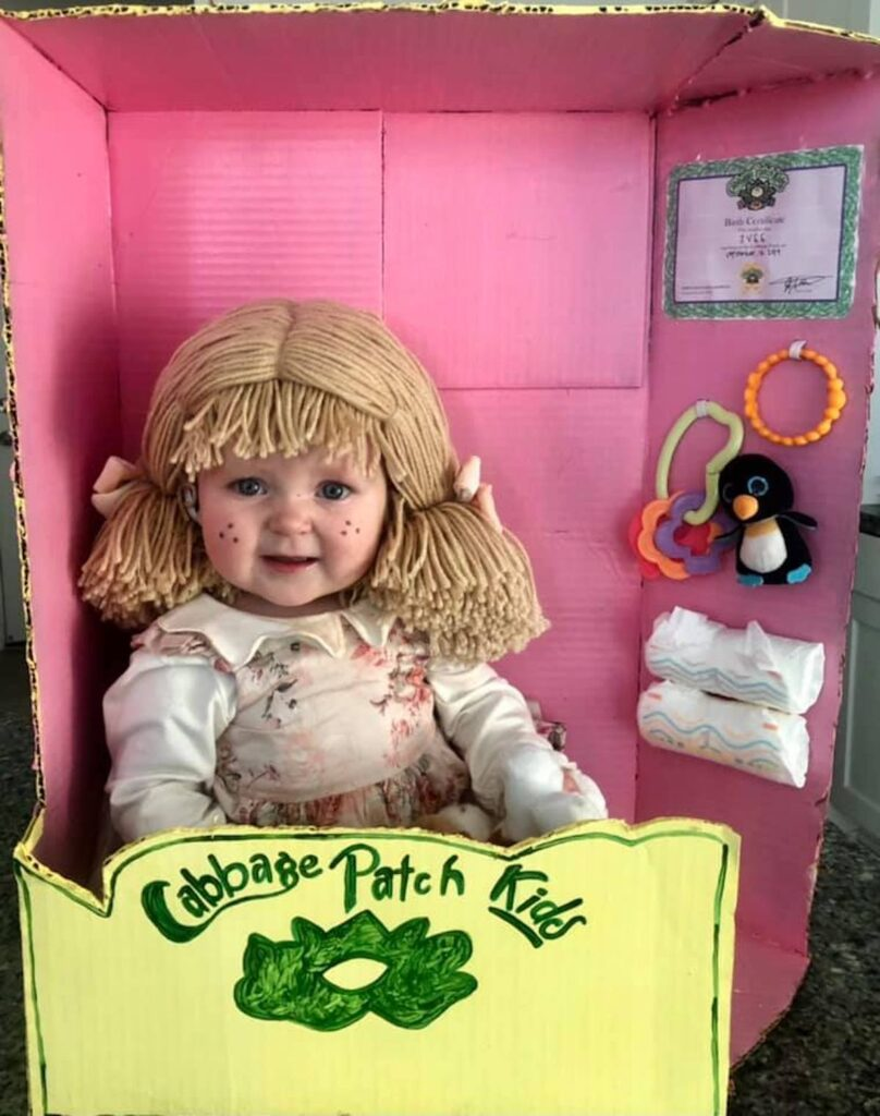 Baby girl wearing Cabbage Patch Doll costume sits in DIY doll box.