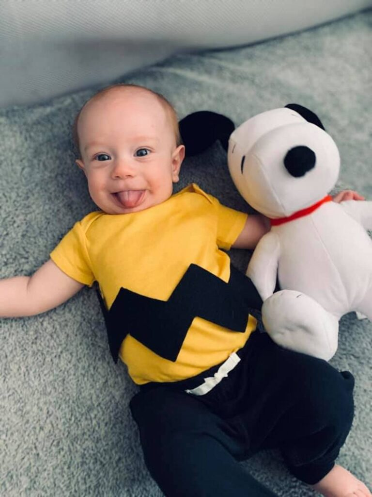 Baby boy wears Charlie Brown costume and lays next to Snoopy dog.