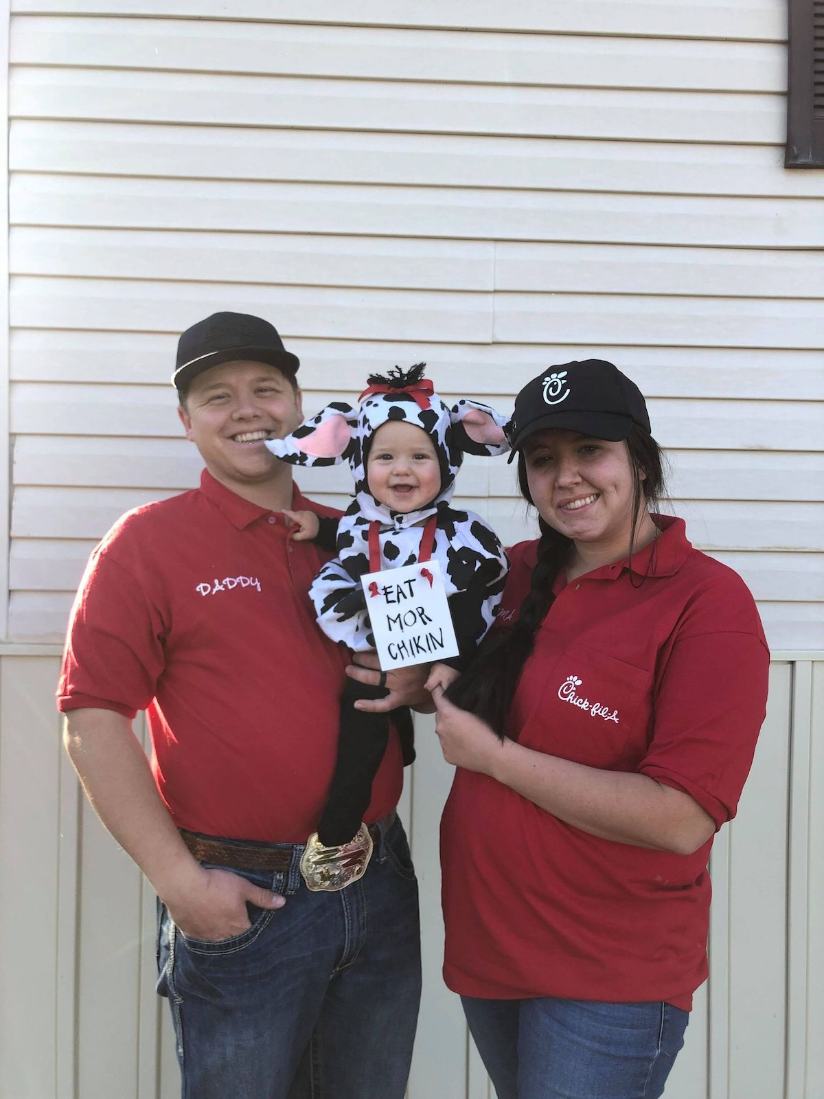 Man and woman wear Chick Fil A shirts and hold baby girl wearing cow costume.
