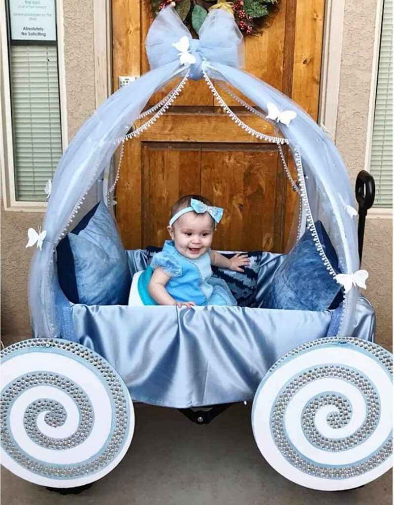 Baby girl wearing Cinderella costume sits in DIY carriage and smiles.