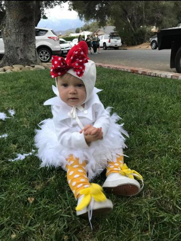 Baby wearing chicken DIY Halloween costume sits on grass.
