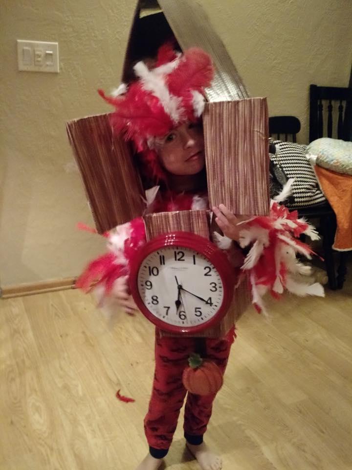 Boy wearing DIY cuckoo clock Halloween costume smiles and stands in living room.