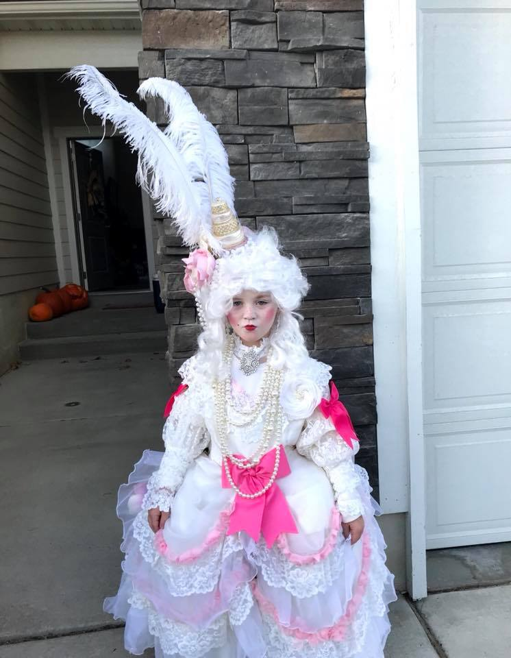 Girl wearing ornate Marie Antoinette Halloween costume and make up stands in front of house