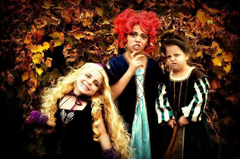 Three girls wearing Hocus Pocus kids Halloween costumes pose for a picture.