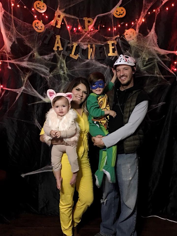 Family dressed in TMNT Halloween costumes smiles in front of photo backdrop.