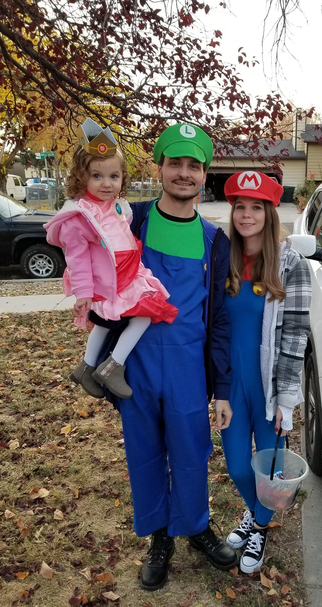 Family wearing Super Mario Halloween costumes smiles in front yard for picture.
