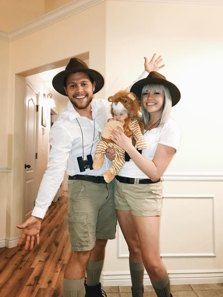 Family wearing safari Halloween costumes poses for picture near white wall.