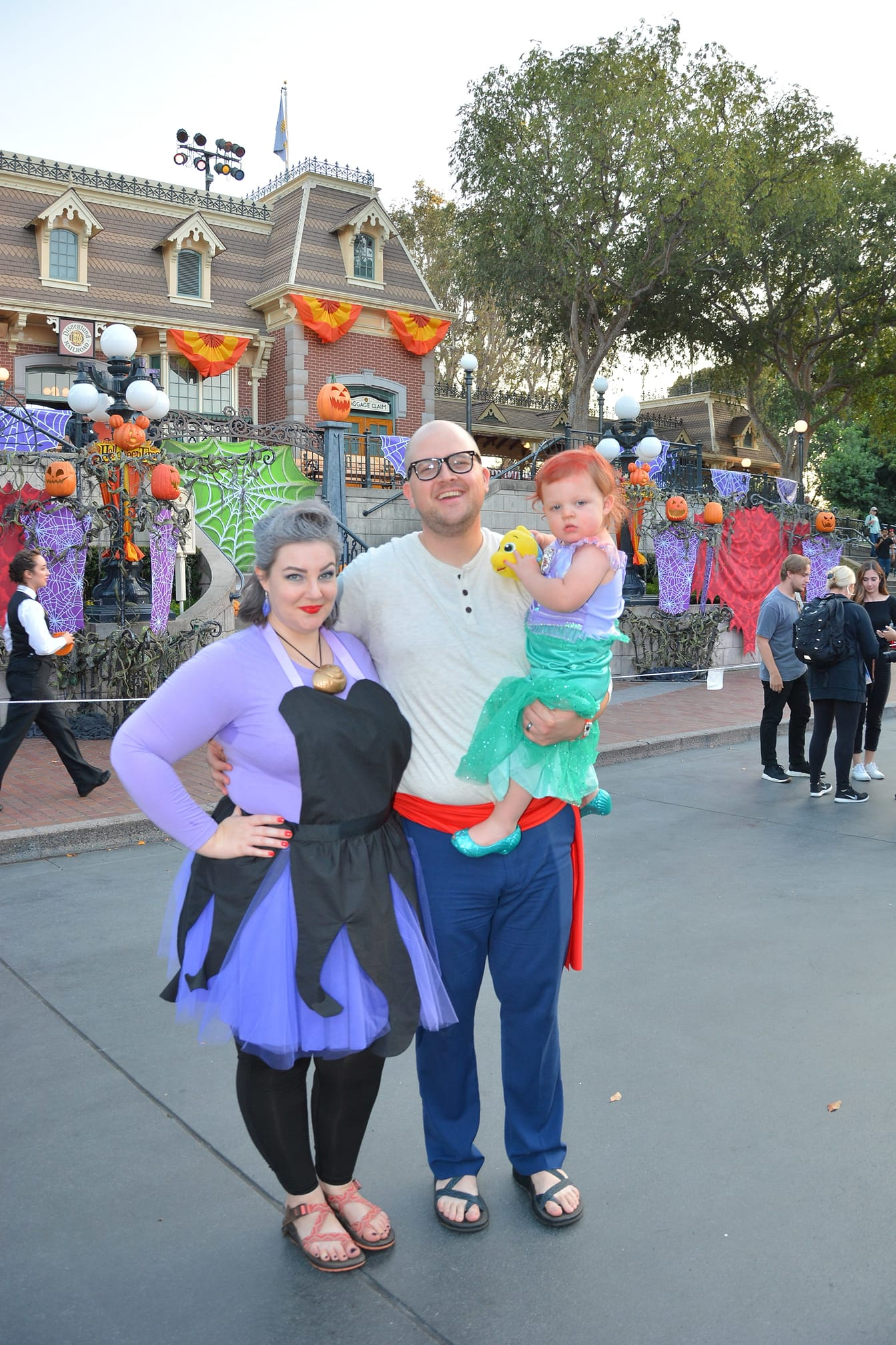 Family dresses as characters from Little Mermaid smiles on Disneyland's main street.