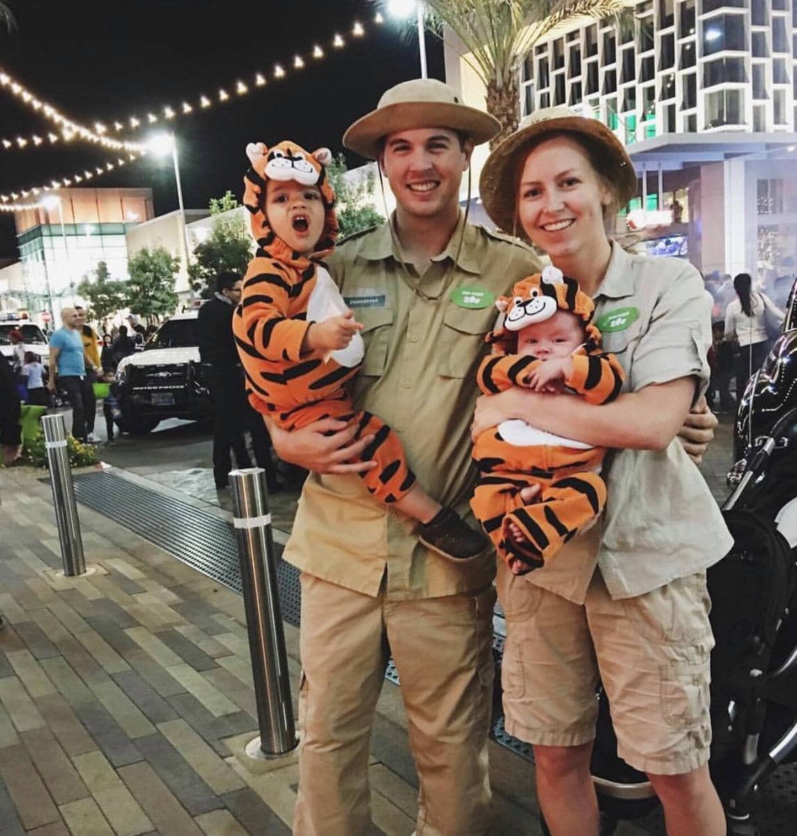 Family wearing zookeeper and animal Halloween costumes poses for picture.