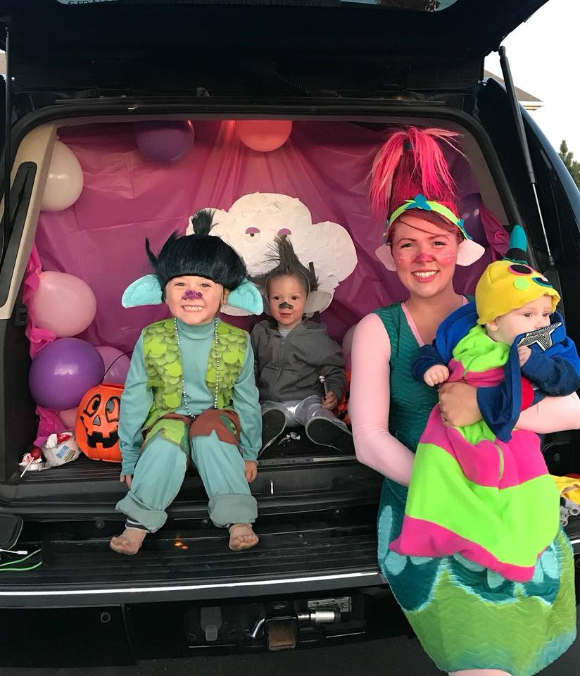 Family wearing Trolls Halloween costumes sits in back of decorated car trunk.