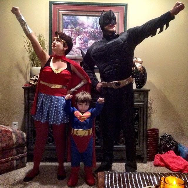 Family wearing superhero Halloween costumes poses for picture in living room.