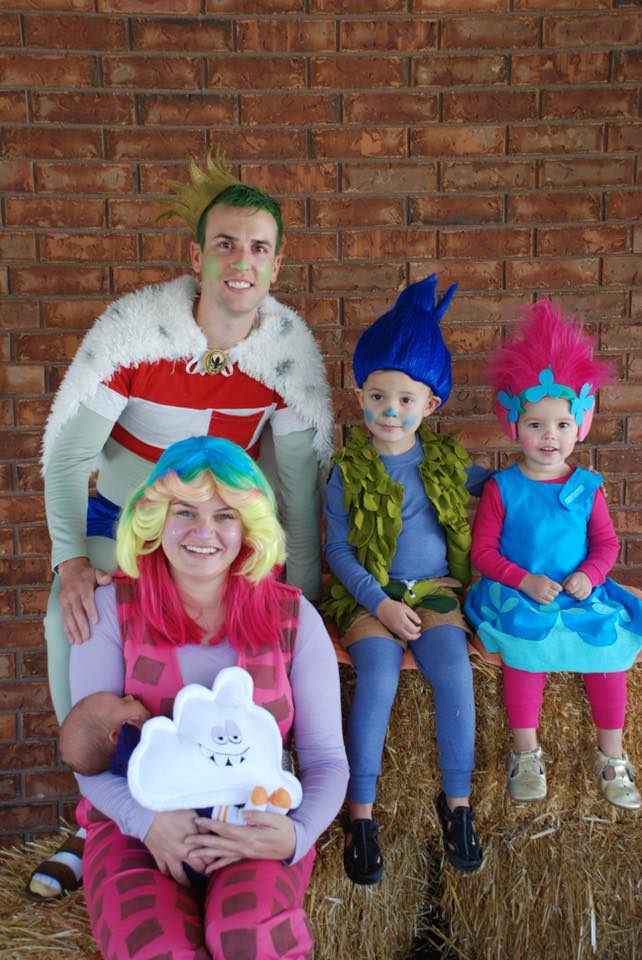 Family wearing Trolls Halloween costumes sits on bales of hay and smiles.