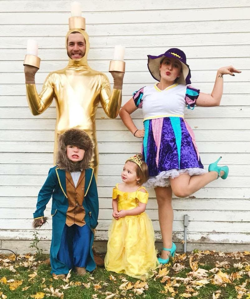 Family wearing Beauty and the Beast Halloween costumes poses in front of white wood wall.