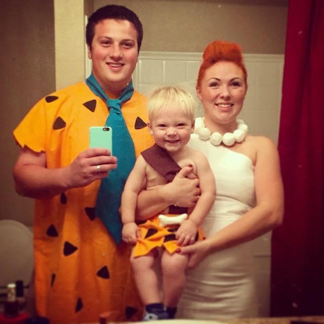 Family wearing Flinstones Halloween costumes takes picture in bathroom mirror.