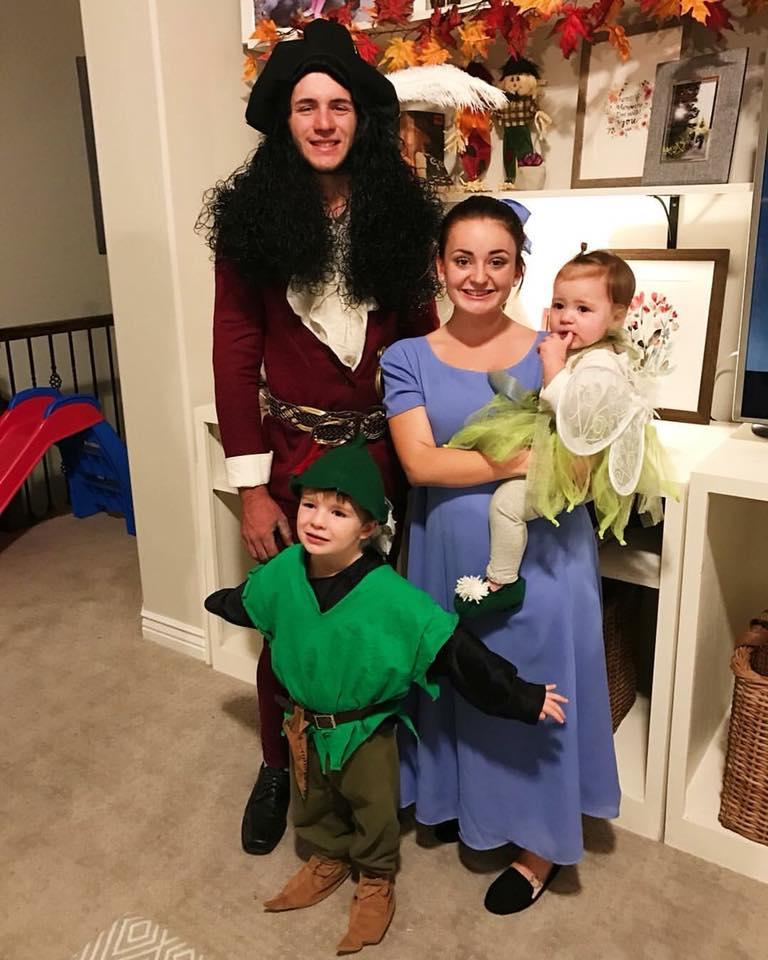 Family wearing Peter Pan Halloween costumes smiles in living room.