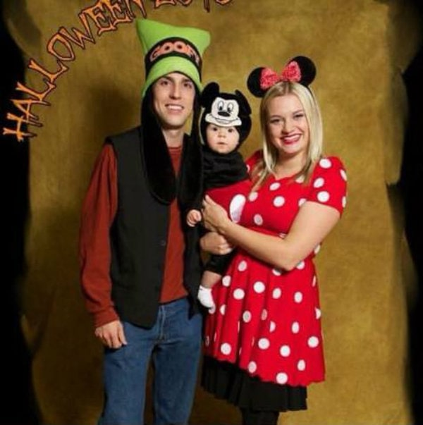 Family wearing Mickey, Minnie, and Goofy costumes smile in front of photo backdrop.