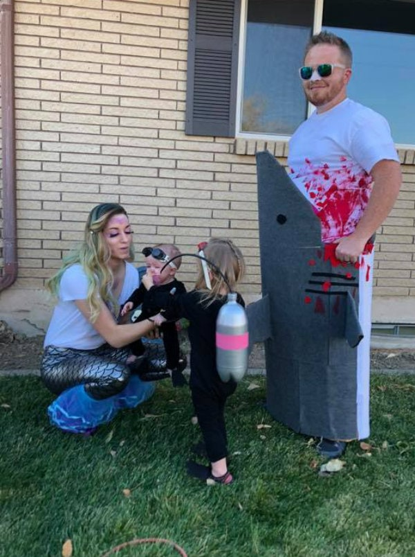 Family wearing mermaid, scuba diver, and shark attack Halloween costumes stands in front yard.