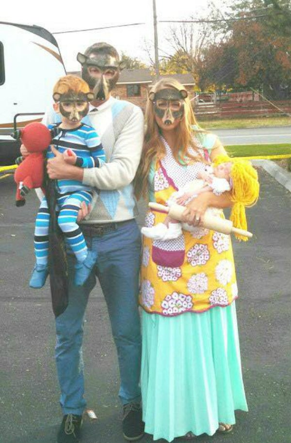 Family dressed as Goldilocks and the three bears stands in parking lot.